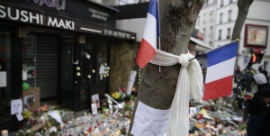 """French flags and a note reading """"We will not let you spoil our children's lives"""" at the site of the attack at the Cafe Belle Equipe on rue de Charonne in the 11th district, early on November 16, 2015 in Paris, three days after the terrorist attacks that left over 130 dead and more than 350 injured. France prepared to fall silent at noon on November 16 to mourn victims of the Paris attacks after its warplanes pounded the Syrian stronghold of Islamic State, the jihadist group that has claimed responsibility for the slaughter.  AFP PHOTO / KENZO TRIBOUILLARD        (Photo credit should read KENZO TRIBOUILLARD/AFP/Getty Images)"""